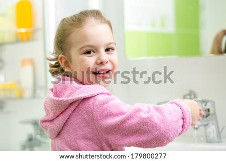kid girl washing her hands in bathroom - stock photo