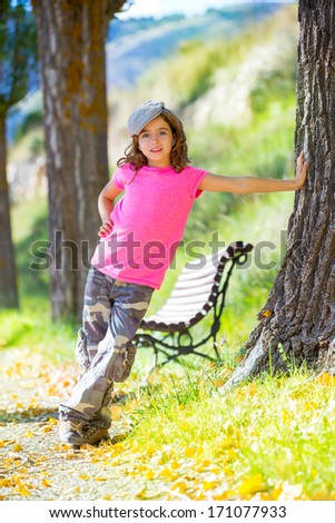kid girl with camouflage pants and cap in park bench outdoor with pink t-shirt - stock photo