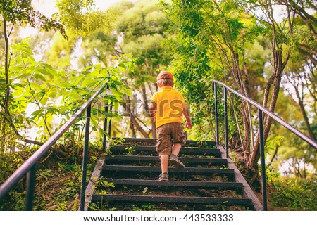kid goes up the stairs in the park. concept of growing up. step by step the child rises higher and goes farther - stock photo