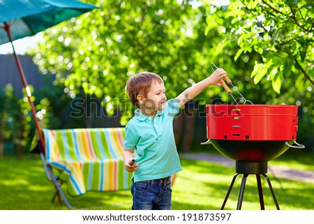 kid grilling food on backyard party - stock photo