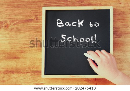 kid hand holding chalk over blackboard with the phrase back to school written on it. - stock photo