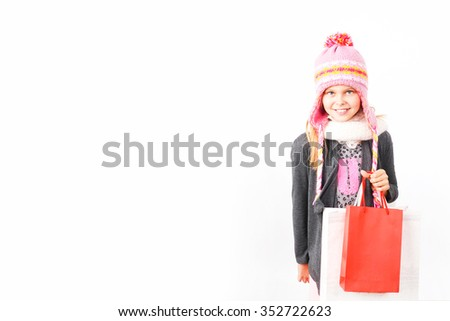 Kid holding Christmas shopping bags in hands - stock photo