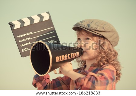Kid holding clapper board against summer sky background. Cinema concept - stock photo