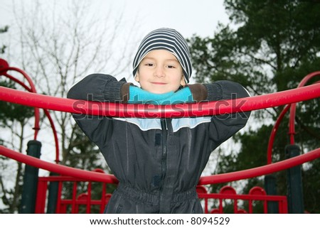Kid in a playground a cold autumn day - stock photo
