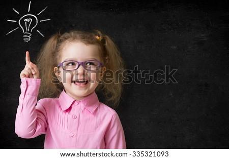 kid in glasses with idea lamp on school chalkboard - stock photo