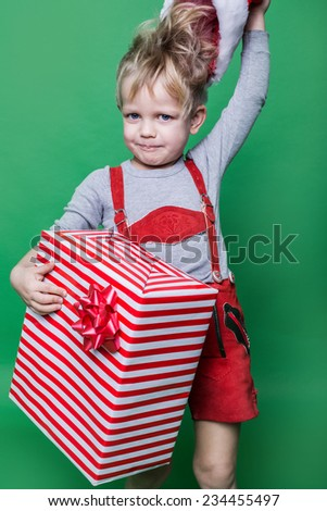 Kid in red costume of dwarf holding Christmas gift and throws Santa Claus cap. Naughty child. Studio portrait over green background - stock photo