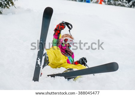 Kid in winter outfit lying in snow with skis - stock photo