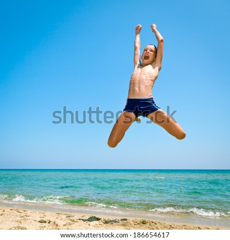 Kid jumping on the beach - stock photo