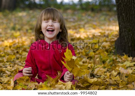 Kid laughing in the park sitting on the ground full of fallen leaves - stock photo