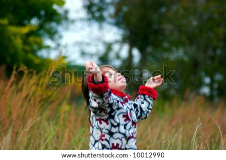 Kid looking up to the sky in the autumn meadow - stock photo