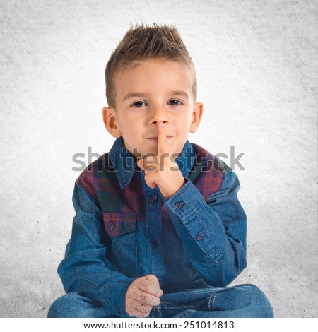 Kid making silence gesture over textured background - stock photo