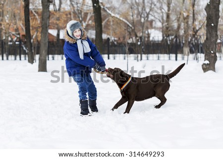 Kid of school age with dog in winter park - stock photo