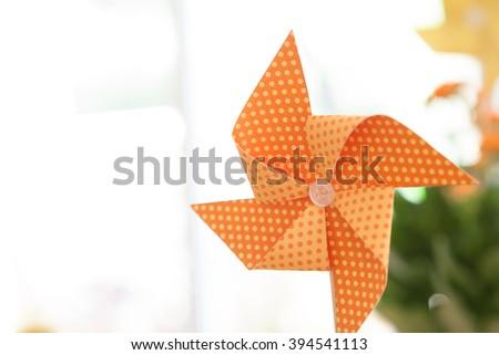 Kid orange windmill toy on white background - stock photo