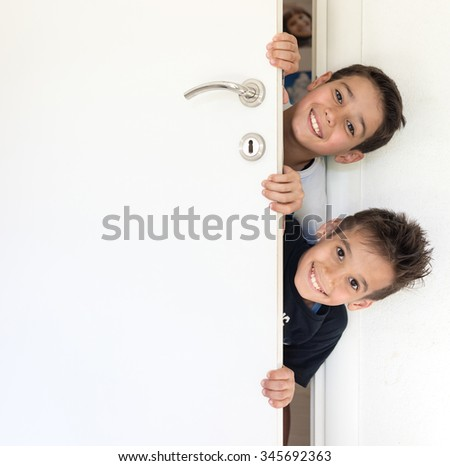 Kid peeking out of the open room door - stock photo