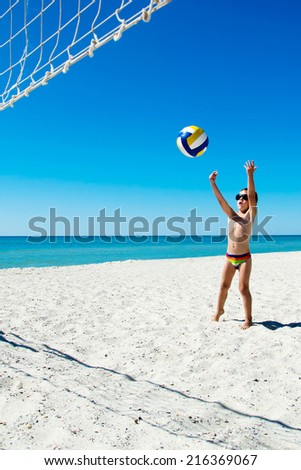 Kid play volleyball on sea beach - stock photo