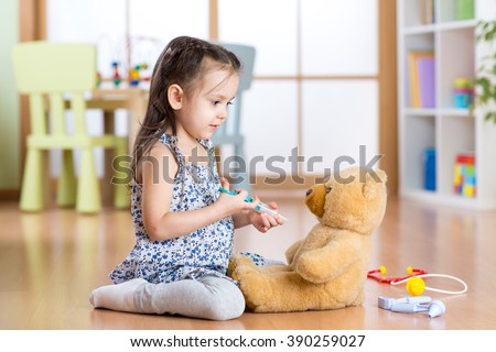 kid playing a doctor in children room - stock photo