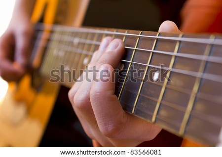 Kid playing acoustic   guitar close-up - stock photo
