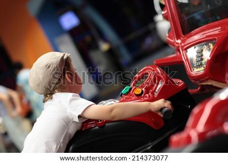 Kid playing arcade simulator machine at an amusement park - stock photo