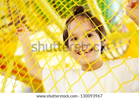 Kid playing at new playground kindergarten behind the net - stock photo