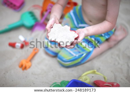 Kid playing in the sandbox, hands in focus - stock photo