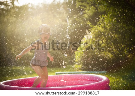 kid playing in water during summertime - stock photo