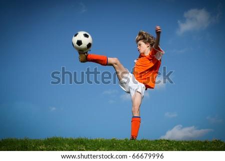 kid playing soccer kicking football - stock photo