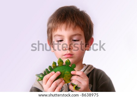 Kid playing with a dinosaur toy - stock photo