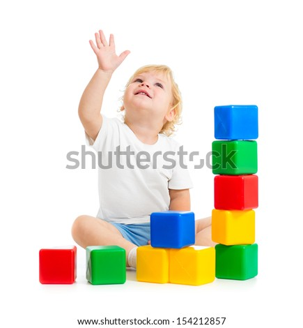 kid playing with colorful building blocks and looking up - stock photo