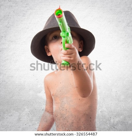 Kid playing with plastic gun - stock photo