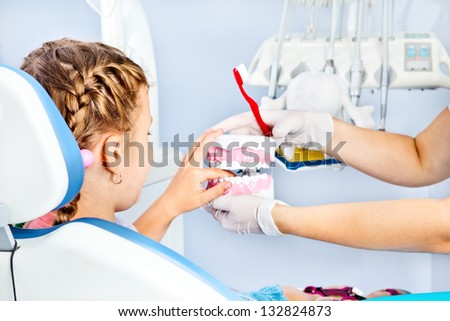 Kid playing with toy dentures in the dentist's office - stock photo