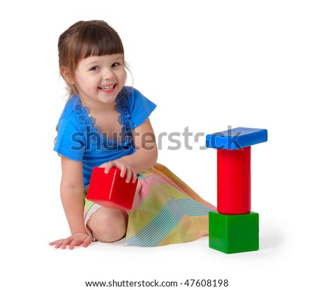 Kid playing with toys. Little girl in dress holding in hand color blocks isolated on white background - stock photo