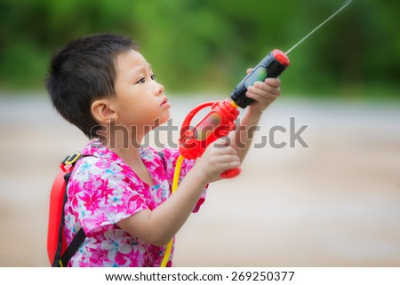 Kid playing with water toy in the Songkran festival - stock photo