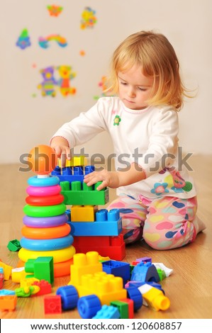 Kid playing with wooden blocks laying on the floor in their room - stock photo
