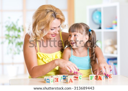 kid plays building blocks with parent at home - stock photo