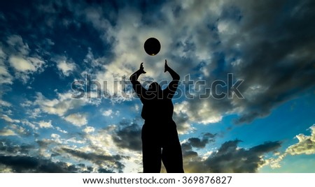 Kid plays with ball during evening in silhouette - stock photo