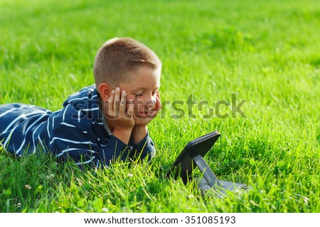 Kid reading an ebook, tablet in a park over green grass - stock photo