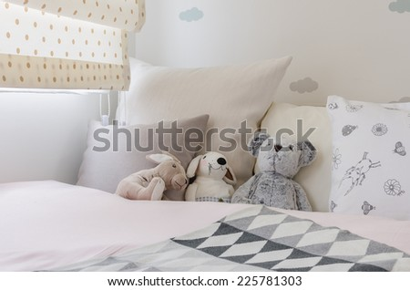 kid's bedroom with dolls and pillows on bed at home - stock photo