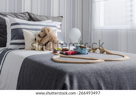 kid's bedroom with dolls and toys on bed in black and white style at home - stock photo