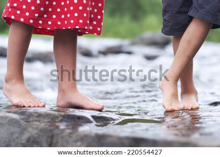 Kid's feet wading in shallow water - stock photo
