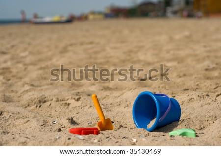 Kid's sand blue pail on beach - stock photo