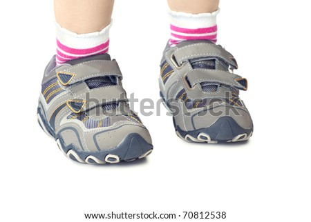 Kid`s sneakers. Closeup of child legs wearing shoes. Isolated on white background. - stock photo