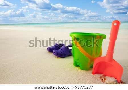 Kid's toys and boots on the beach sand near the ocean waters - stock photo