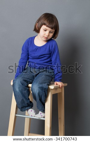 kid serenity concept - thinking preschool child looking down in sitting on high wooden stool for serene wellbeing,studio shot - stock photo