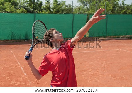 Kid serving the ball - stock photo