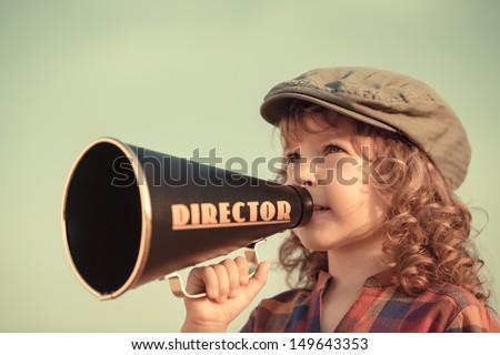 Kid shouting through vintage megaphone. Communication concept. Retro style - stock photo