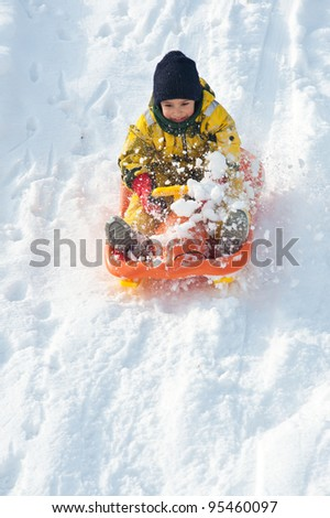 Kid sliding with bob in the snow. - stock photo