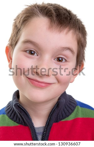 Kid smiling mischievously happy, perhaps just did something wrong. - stock photo