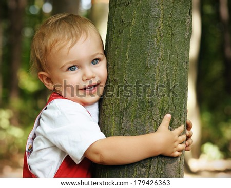 Kid standing near the tree in the park  - stock photo