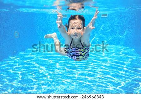 Kid swims in pool underwater, girl swimming, playing and having fun, children water sport  - stock photo