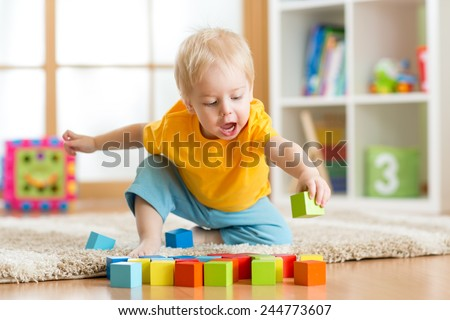 kid toddler playing  wooden toys at home or nursery - stock photo